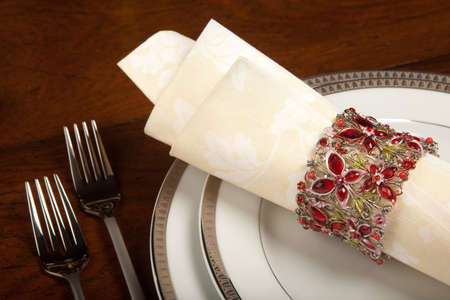 napkin ring: Cream colored festive napkin with ornate fancy napkin ring on a holiday table