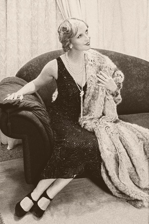 Fancy lady in 1920s style sitting on a luxury chaise-longue - noise has been added for vintage effect photo