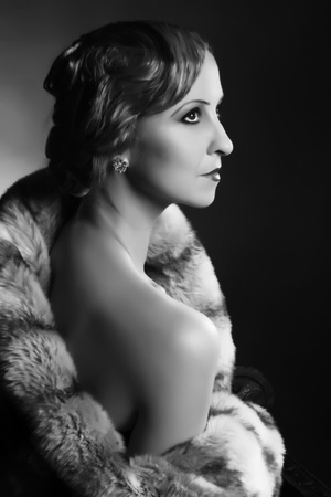 Retro image in black and white featuring a classy lady posing in 1920s hollywood style photo
