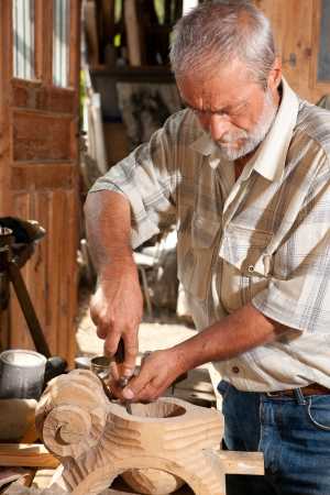 sculpting: Senior carpenter working with wood in his old shed Stock Photo