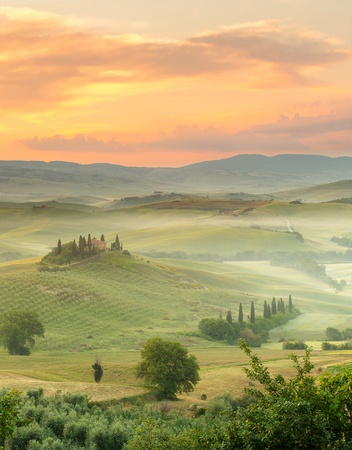Dawn in a misty valley with view on Bevedere villa in the hills of San Quiricy d'Orcia photo