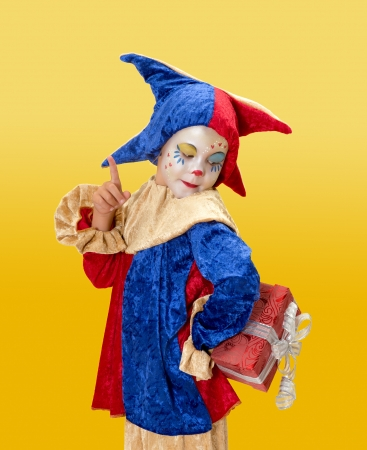 harlequin clown in disguise: Cute young clown girl hiding a present behind her back Stock Photo