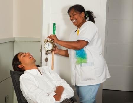 mujer limpiando: Limpieza mujer sosteniendo un reloj despertador junto a un empleado de oficina para dormir