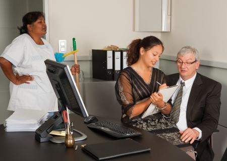dictating: Limpieza mujer viendo una secretaria sentada en el regazo de su jefe