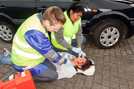 Paramedics checking a woman injured during a car accident (the sleeve badges have been replaced by a non existing logo) photo