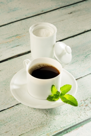 sweetening: Coffee cup and a pot of white natural sweetener stevia