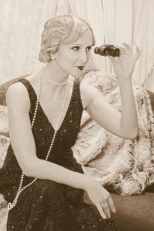 Old photo with reenacted scene of a classy lady in roaring twenties style using a pair of opera glasses - grain has been added for vintage photo look photo