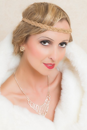 Beauty portrait of a vintage style woman with twenties headband and white fur photo