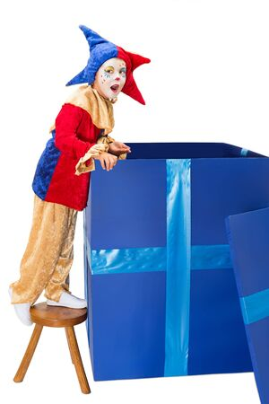 harlequin clown in disguise: Little jester clown looking into a big blue surprise box