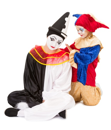 Sad pierrot getting consolation by a little girl clown photo