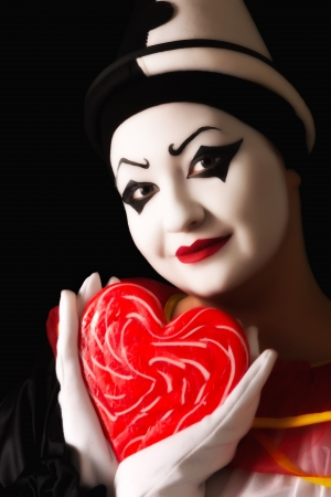 pierrot: Beautiful pierrot clown in love with a red candy heart Stock Photo