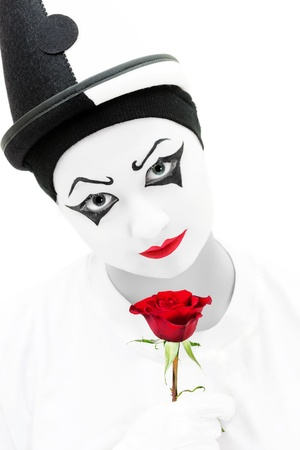 Unhappy Pierrot in high key black and white with a red rose photo