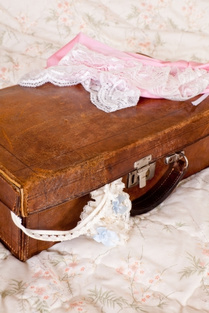 Bed with vintage leather suitcase and sexy bridal lingerie photo