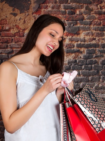 Happy young woman looking at baby socks she has just been shopping for Stock Photo - 17213731