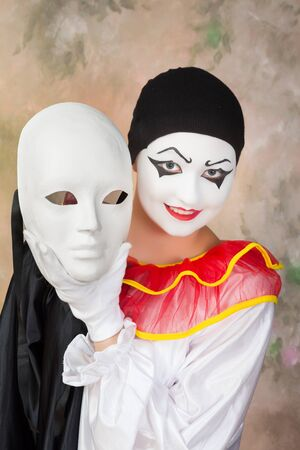 Smiling pierrot holding a sad white mask Stock Photo - 17341893