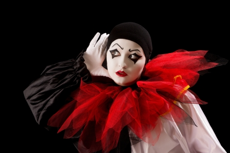 pierrot: Mime Pierrot actor holding her hands as in listening Stock Photo