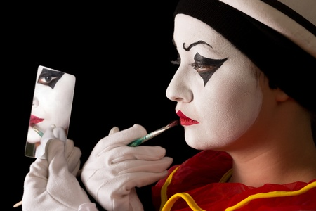 Mime performer applying Pierrot face paint with a brush photo