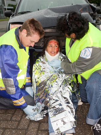 Paramedics putting a protective blanket on a car crash victim (the sleeve badges have been replaced by a non existing logo) photo