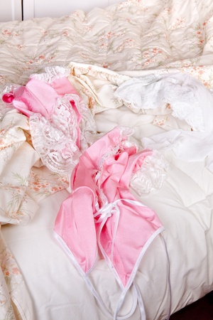 Messy bed with a sexy pink baby-doll Stock Photo - 17346563