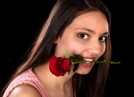 Beautiful brunette with a red rose between her teeth Stock Photo - 17341900