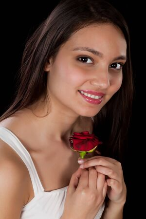 Happy young woman holding a given red rose close to her heart Stock Photo - 17341905