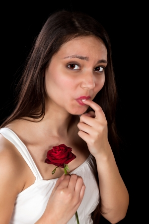 Woman hurting her finger on a red rose photo