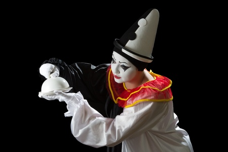 uncovering: Curious Pierrot clown uncovering the lid of a dish