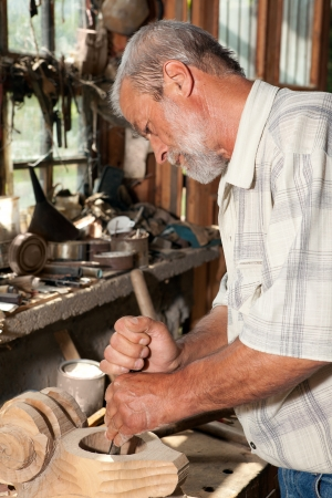 Experienced carpenter shaping wood in his old shed photo