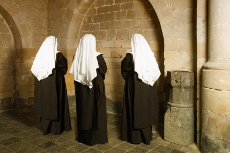 carmelite nun: Young nuns facing the walls of a 14th century medieval abbey