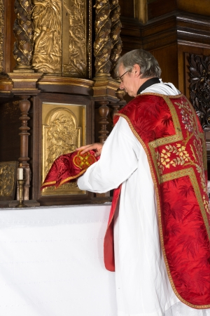 vestment: Catholic priest putting a covered chalice back into the tabernacle of a medieval church with 17th century interior