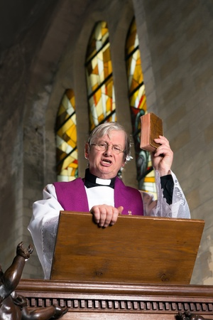 Rijpe prediker op houten preekstoel tijdens de mis Stockfoto