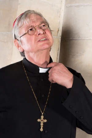 pinching: Mature cardinal annoyed by the pinching priest collar in his shirt or cassock Stock Photo