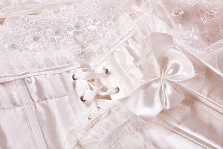 Closeup of a white wedding corset and veil on a bedsheet photo