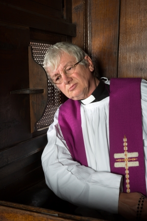 Vicar listening to the sins of a person in the confession booth photo