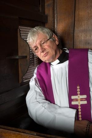 Vicaris luisteren naar de zonden van een persoon in de belijdenis stand Stockfoto