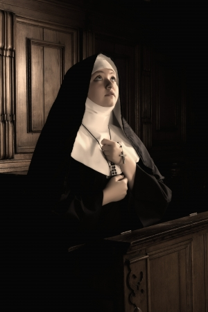 Desaturated image of a young novice nun praying a rosary  Stock Photo - 17667998