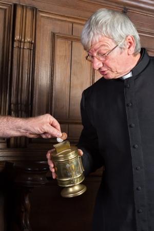 sacerdote: Sacerdote recoger el dinero en la iglesia para recaudar fondos