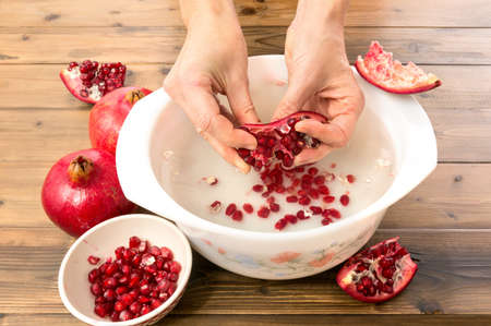 superfruit: Collecting technique for pomegranate seeds in water, making the membrane float and the arils sink Stock Photo