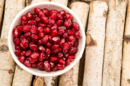 tannins: Small bowl filled with ruby red antioxidant pomegranate seeds