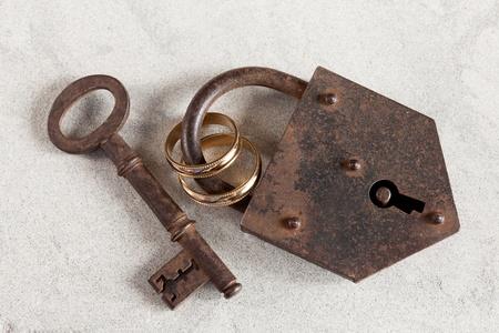 wedlock: Wedding rings boud by a rusty old padlock Stock Photo