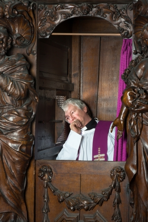 confession: Priest sitting in 17th century confession booth listening to the repentant Stock Photo