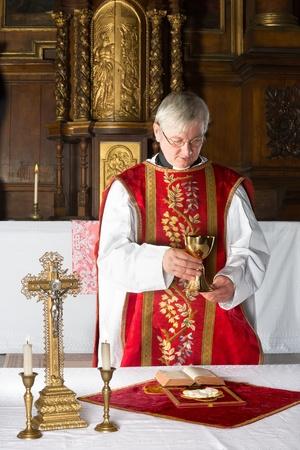 eucharistie: Prêtre catholique cours de la consécration d'une église médiévale avec un intérieur du 17ème siècle Banque d'images