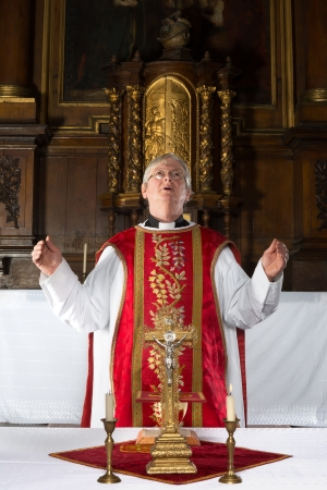 mass: Catholic priest saying a prayer during mass in a medieval church with 17th century interior (including the painting)