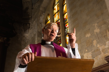Vicar talking on his pulpit in a 17th century old church Stock Photo