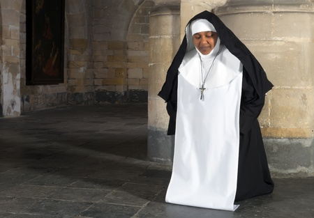 african worship: Kneeling nun in a medieval interior of a 14th century Belgian church