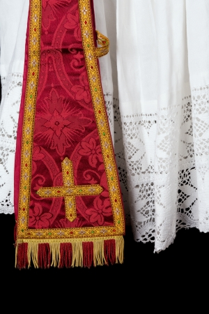catholic mass: Antique red maniple hanging over the lace edge of an old priest surplice