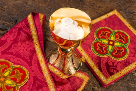 vestment: Communion scene of a chalice with vestment set and wafers