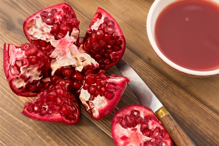 tannins: Detailed close up of a fresh pomegranate and bowl of juice