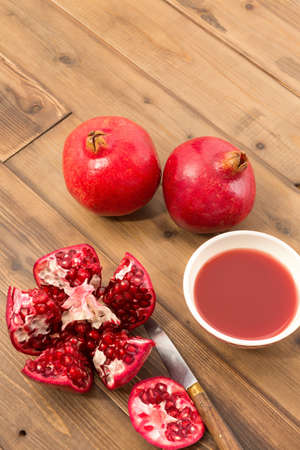 Wooden table with cut pomegranate and bowl of fresh juice Stock Photo - 17779546