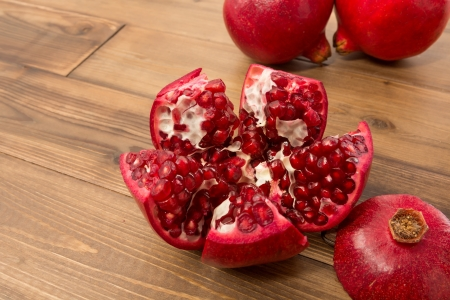 Two whole and one cut open pomegranate on a wooden table Stock Photo - 17779543
